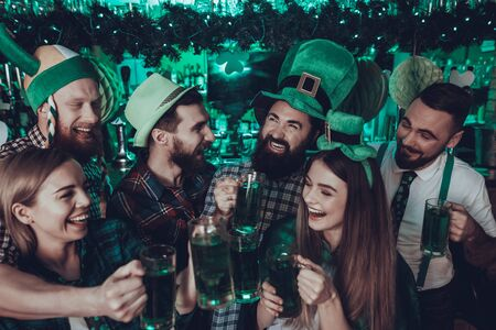 Saint Patrick's Day Party. Group of Friends and Barman is Celebrating. Happy People is Toast and Drinking a Green Beer.