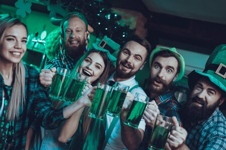 Saint Patrick's Day Party. Group of Friends is Celebrating. Happy People is Toast and Drinking a Green Beer. Friends is Young Men and Women. People Wearing a Green Hats. Pub Interior. Stock Photo