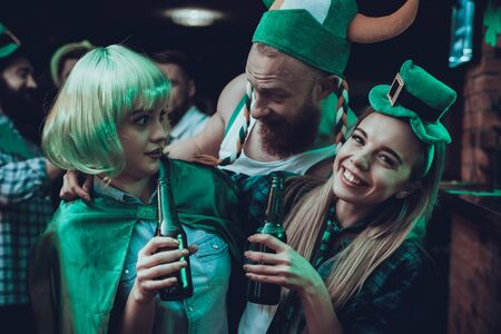 Saint Patrick's Day Party. Group of Friends is Celebrating. Happy People is Drinking a Green Beer. Friends is Young Men and Women. Man is Scares a Girl. People Wearing a Green Hats. Pub Interior.