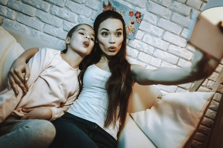 Mother with Daughter is Sitting on Couch.