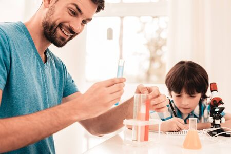 Youn Bearded Father Teaching Son in Shirt at Home. Education at Home. Using Microscope. Studding Chemistry. White Table in Room. Sitting Boy. Young Father. Lesson at Home. Education Concept.