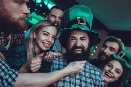 Saint Patricks Day Party. Friends is Celebrating. Happy People is Drinks a Green Beer. Friends is Young Men and Women. Man is Touching the Beard of Friend. People Wearing a Green Hats. Pub Interior.