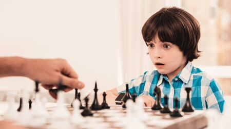 Bearded Father and Son Playing Chess on Table. Happy Family Concept. Board on Table. Young Boy in Shirt. Imagens