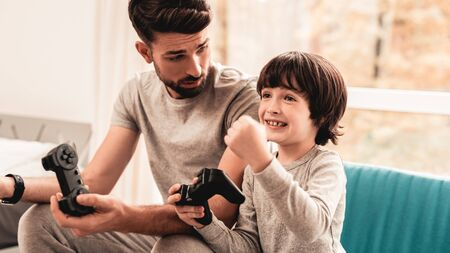 Father and Son Sitting and Playing on Console. Sitting Boy. Young Father. Playing on Console. Joystick in Hands.