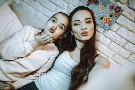 Mother with Daughter is Sitting on Couch. People Doing a Selfie on Mobile Phone. Mother with Daughter is Showing a Lips and Kissing. Stockfoto - 128616579