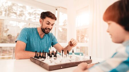 Bearded Father and Son Playing Chess on Table. Happy Family Concept. Board on Table.