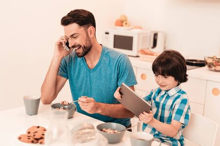 Happy Young Father and Son Using Tablet at Home. Smiling Boy. Modern Kitchen. Sitting Boy. Boy in Shirt. Breakfast in Morning.