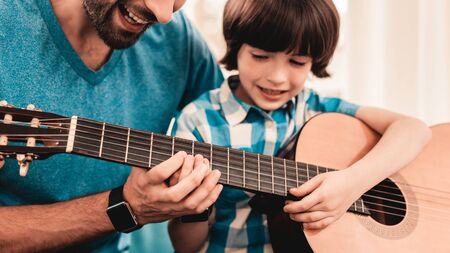 Young Bearded Father Playing on Guitar with Son. Happy Family Concept. Musician at Home. Zdjęcie Seryjne