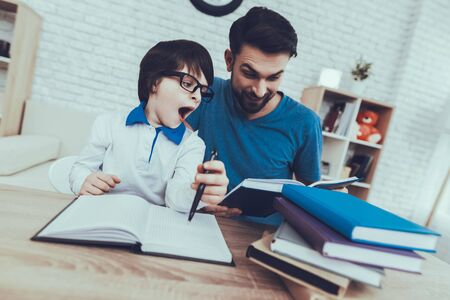 Man Spends Time with His Son. Father of Boy is Engaged in Raising Child. Smiling Father is Reading a Book. Boy in Glasses is Yawning. People is Sitting at Table. People Located at Home.