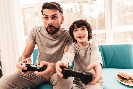 Father and Son Sitting and Playing on Console. Sitting Boy. Young Father. Playing on Console. Joystick in Hands. Young Bearded Man at Home. Sitting on Blue Sofa. Happy Family Concept. Imagens