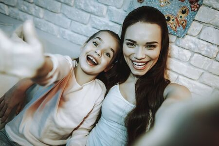 Mother with Daughter is Sitting on Couch. People Doing a Selfie on Mobile Phone. Mother with Daughter is Happy and Smiling.