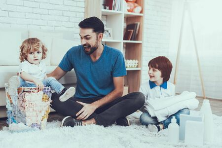 Father is Engaged in Raising Children. Father is Teaching a Sons a Cleaning. People Want to Wash a Dirty Clothes. Younger Son is Sitting in Basket with Clothes. People is Located in Bedroom on Carpet. Standard-Bild