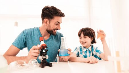 Bearded Father Teaching Son in Shirt at Home. Education at Home. Using Microscope. Studding Chemistry. Standard-Bild