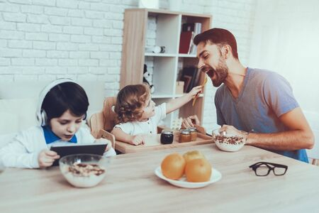 Man Spends Time with His Sons. Father of Boys is Engaged in Raising Children. Father is Feeding a Younger Son. Eldest Son is Watching Video on Tablet PC. Boys is Sitting at Table. People on Kitchen. Reklamní fotografie - 127905197