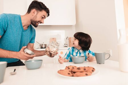 Smiling Son and Father Have Breakfast in Kitchen. Boy in Shirt. Modern Kitchen. Sitting Boy. Boy with Spoon. Breakfast in Morning. White Table in Kitchen. Gray Bowl on Table. Young Father.