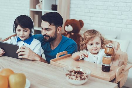 Father of Boys is Engaged in Raising Children. Eldest Son with Father is Watching Video on Tablet PC. Younger Son is Builded Tower from Baby Food. Boys is Sitting at Table. People Located on Kitchen.
