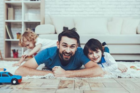 Man Spends Time with His Sons. Father is Engaged in Raising Children. Father and Eldest Sons is Lying on Carpet and Smiling. Younger Son is Playing Alone on Background. People is Located in Bedroom. Reklamní fotografie - 127905186