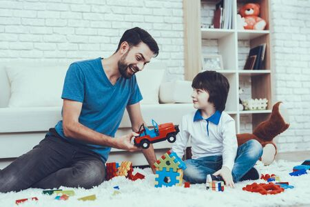 Man Spends Time with His Son. Father of Boy is Engaged in Raising Child. Father and Son is Playing with Toys. Persons is Sitting on Carpet. People is Located in Bedroom. Stok Fotoğraf
