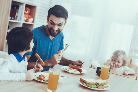 Man Spends Time with His Sons. Father of Boys is Engaged in Raising Children. Eldest Son and Father is Eating a Breakfast and Smiling. People is Sitting at Table. People Located on Kitchen.