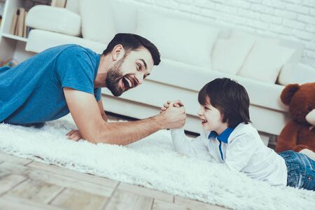 Man Spends Time with His Son. Father of Boy is Engaged in Raising Child. Father and Son is Playing in Arm wrestling. Persons is Lying on Carpet and Smiling. People is Located in Bedroom.