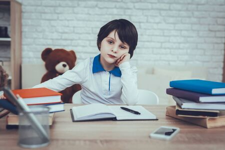 Child is Doing Homework. Child is a Little Black Haired Boy. Boy is Upset. Child Sitting at Table. Books and Mobile Phone on Table. Boy Located at Home. Child Looking into a Camera.
