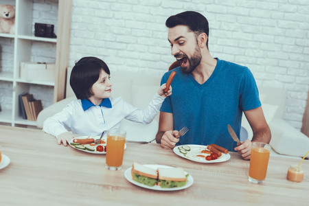 Man Spends Time with His Son. Father of Boy is Engaged in Raising Child. Father is Feeding a Son a Breakfast. Son is Giving a Sausage to Father. People is Sitting at Table. People Located on Kitchen.