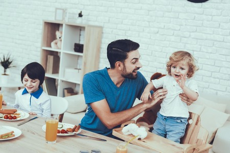 Man Spends Time with His Sons. Father of Boys is Engaged in Raising Children. Eldest Son is Eating a Breakfast. Father is Calms the Upset Son. People is Sitting at Table. People Located on Kitchen.