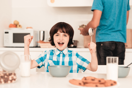 Little Boy in Shirt Have Fun in Kitchen in Morning. Son with Father. Modern Kitchen. Sitting Boy. Boy with Spoon. Breakfast in Morning. White Table in Kitchen. Gray Bowl. Young Father.