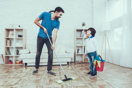 Man Spends Time with His Son. Father of Boy is Engaged in Raising Child. Father is Teaching a Son a Cleaning. Father and Son Washing the Floor with Mop. People is Located in Bedroom.