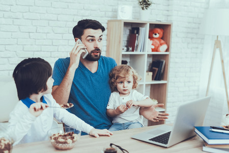 Father is Engaged in Raising Children. Eldest Son is Eating a Breakfast. Father is Working and Talking on Cellphone. Man is Holding a Younger Son. People is Sitting at Table. People Located at Home.