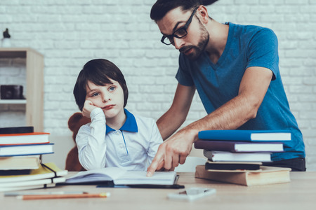 Man Spends Time with His Son. Father of Boy is Engaged in Raising Child. Father in Glasses Pointing on Homework to Son. Boy is Sad. Eldest Son is Sitting at Table. People Located at Home. Reklamní fotografie - 127586834