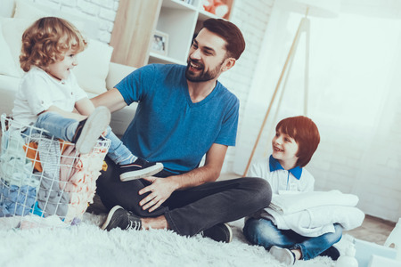 Father is Engaged in Raising Children. Father is Teaching a Sons a Cleaning. People Want to Wash a Dirty Clothes. Younger Son is Sitting in Basket with Clothes. People is Located in Bedroom on Carpet. Stock Photo