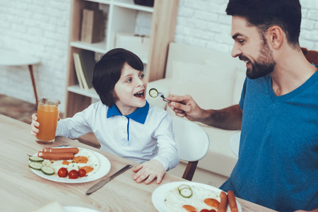Man Spends Time with His Son. Father of Boy is Engaged in Raising Child. Father is Feeding a Son a Breakfast. Father is Giving a Cucumber to Son. People is Sitting at Table. People Located on Kitchen. Reklamní fotografie