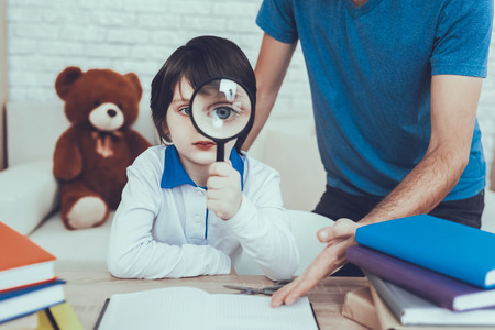 Man Spends Time with His Son. Father is Engaged in Raising Child. Father Pointing on Homework to Son. Boy is Looking Through Magnifying Glasses. Eldest Son is Sitting at Table. People Located at Home. Reklamní fotografie - 127586712