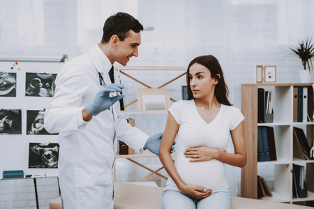 Pregnant Girl at the Gynecologist Doctor. Doctor is a Young Smiling Man. Doctor is Showing the Pregnancy Test to Woman. Girl is Sitting on Couch and Touching Her Belly. People Located at Clinic.