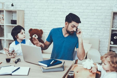 Man Spends Time with His Sons. Father is Engaged in Raising Children. Eldest Son is Eating a Breakfast. Father is Working and Talking on Cellphone. People is Sitting at Table. People Located at Home.