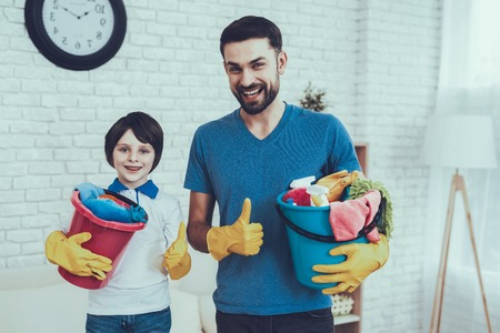 Father of Boy is Engaged in Raising Child. Father is Teaching a Son a Cleaning. Persons is Holding a Baskets with Cleaning Supplies. People is Showing OK Sign and Smiles. People is Located in Bedroom.