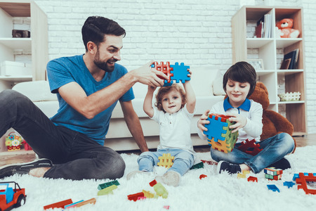 Man Spends Time with His Sons. Father is Engaged in Raising Children. Father and Sons is Playing with Toys. Toys is Lego. Persons is Smiling. Persons is Sitting on Carpet. People Located in Bedroom. Foto de archivo - 127586653