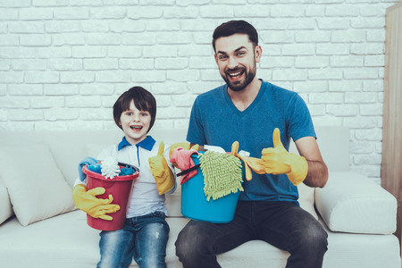 Father is Teaching a Son a Cleaning. Persons is Holding a Baskets with Cleaning Supplies. People is Showing OK Sign and Smiling. Persons is Sitting on Couch. People is Located in Bedroom.