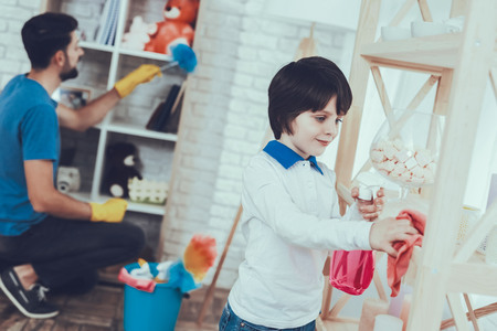 Man Spends Time with His Son. Father of Boy is Engaged in Raising Child. Father is Teaching a Son a Cleaning. Father and Son Wipe the Furniture Surfaces from Dust. People is Located in Bedroom. Stock Photo