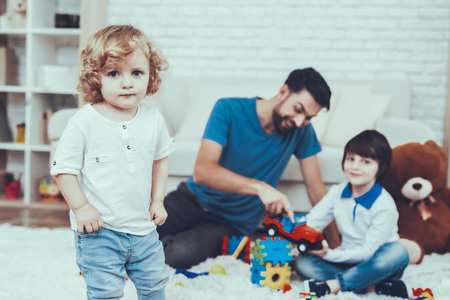 Man Spends Time with His Sons. Father is Engaged in Raising Children. Father and Eldest Sons is Playing with Toys on Carpet. Younger Son is Standing Alone. People is Located in Bedroom. Reklamní fotografie - 127586490