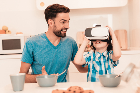 Young Father and Son Using VR Glasses at Home. Smiling Boy. Modern Kitchen. Sitting Boy. Boy in Shirt. Breakfast in Morning. White Table in Kitchen. Using Digital Device. Happy Family.