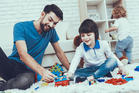 Man Spends Time with His Sons. Father is Engaged in Raising Children. Father and Eldest Sons is Playing with Toys on Carpet. Younger Son is Playing Alone on Background. People is Located in Bedroom.