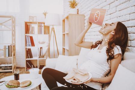 Vrouw eet veel popcorn. Vrouw is een jong donkerbruin zwanger meisje. Meisje zittend op de bank. Vrouw houdt een bord met snacks vast. Ander eten en Cola op tafel. Persoon die zich thuis bevindt. Stockfoto