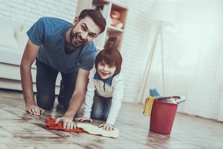 Man Spends Time with His Son. Father is Engaged in Raising Child. Father is Teaching a Son a Cleaning. Father and Son Washing the Floor with Rags. Persons is Smiling. People is Located in Bedroom. Stock Photo