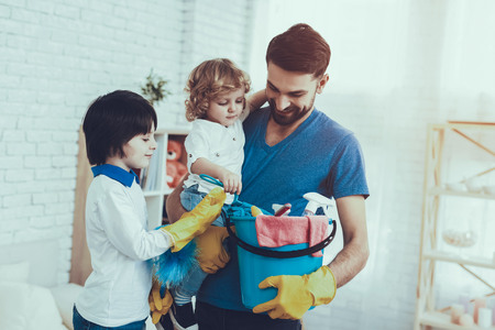 Father of Boy is Engaged in Raising Children. Father is Teaching a Sons a Cleaning. Persons is Holding a Baskets with Cleaning Supplies. People is Smiling. People is Located in Bedroom.