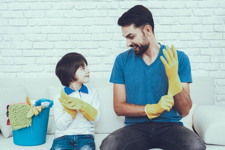 Man Spends Time with His Son. Father of Boy is Engaged in Raising Child. Father is Teaching a Son a Cleaning. Persons Weating a Gloves. Persons is Sitting on Couch. People is Located in Bedroom. Stock Photo