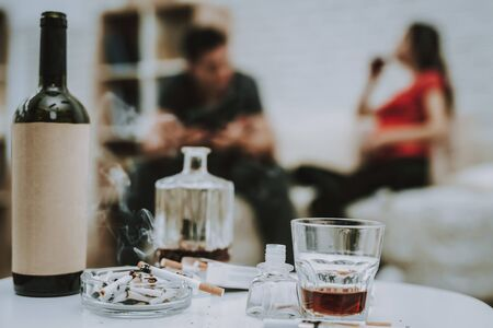 Cigarettes and Alcohol on Table. One Cigarette is Burning. Alcohol is Whiskey and Wine in Bottles. Blur Image of Wife and Husband. Man is Argues with His Pregnant Wife on Background. Closeup.