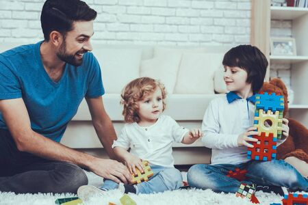 Man Spends Time with His Sons. Father is Engaged in Raising Children. Father and Sons is Playing with Toys. Persons is Sitting on Carpet. People is Located in Bedroom.