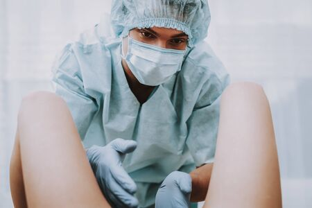 Obstetrician is Taking a Birth. Obstetrician is Adult Man. Man Wearing a Special Medical Uniform. Medical Uniform with Gloves, Cap and Mask. People Located in Clinic. Closeup View. Stock Photo